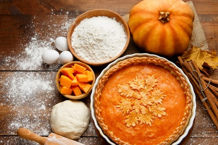 나무 테이블에 베이킹 접시에 전통적인 미국의 신선한 라운드 밝은 오렌지 수 제 호박 파이