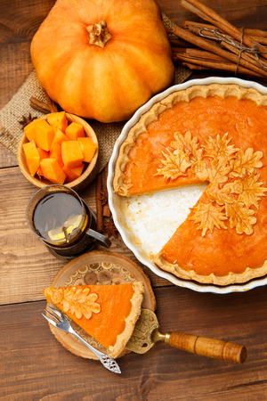 Traditional american fresh round bright orange homemade pumpkin pie in baking dish on wooden table