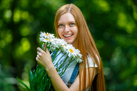 Portrait of beautiful caucasian smiling red-haired young woman, against summer green park. Stock Photo