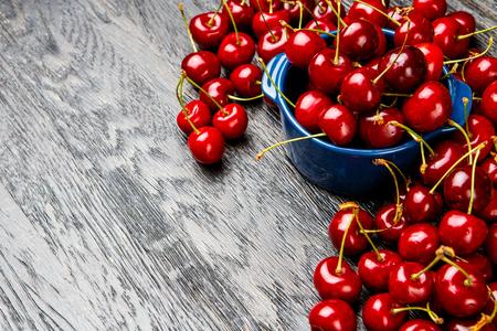 Studio shot of fresh natural cherries on wooden background