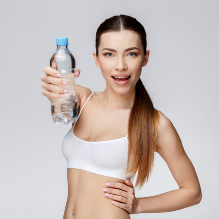 sexualidad: young sporty woman over gray background drinking water