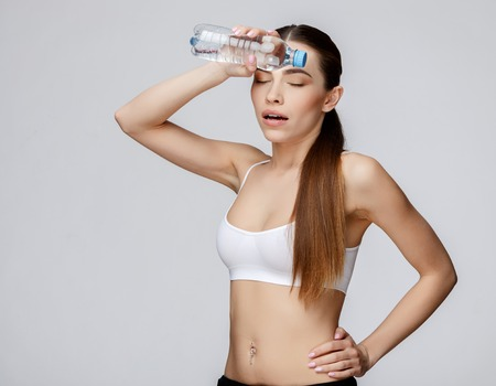 female sexuality: young sporty woman over gray background drinking water