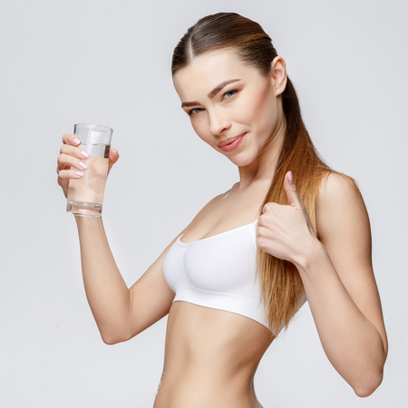 young sporty woman over gray background holding glass of water