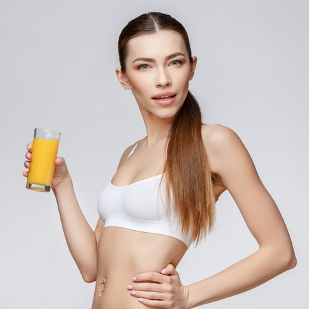 female sexuality: young sporty woman over gray background holding glass of orange juice