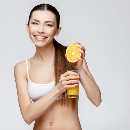 young sporty woman over gray background holding glass of orange juice