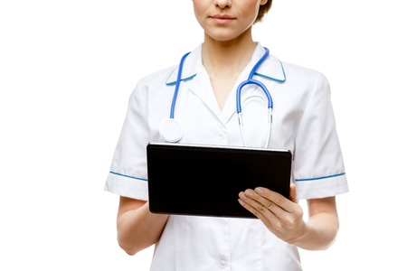 Young woman doctor isolated on white background holding tablet pc