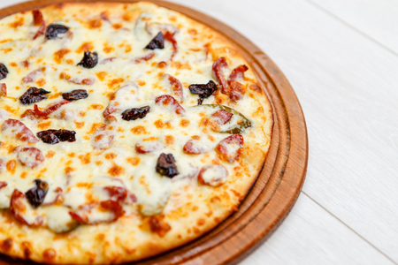color image of fresh tasty pizza on wooden plate Stock Photo