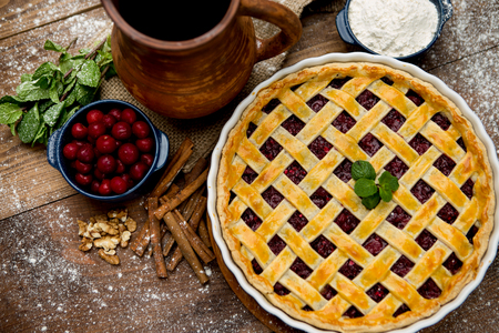 elevated: Homemade cherry pie on wooden table. Elevated view