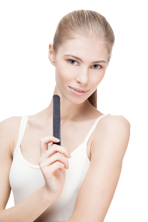 nail file: young blond woman holding nail file isolated on white