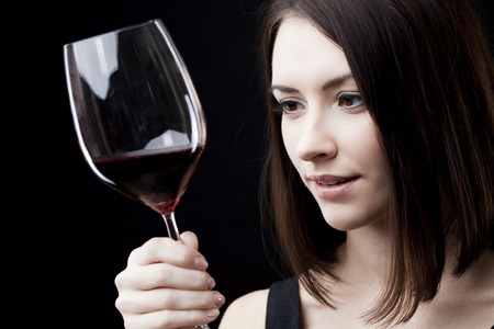 young beautiful woman holding glass of red wine