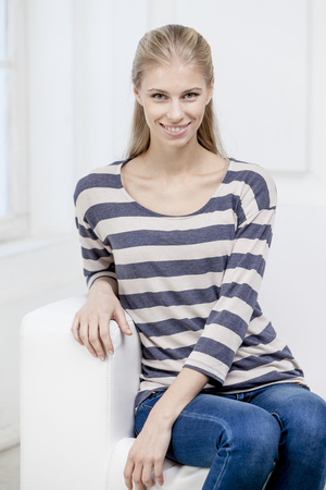 woman on couch: young beautiful blond woman sittin on the couch