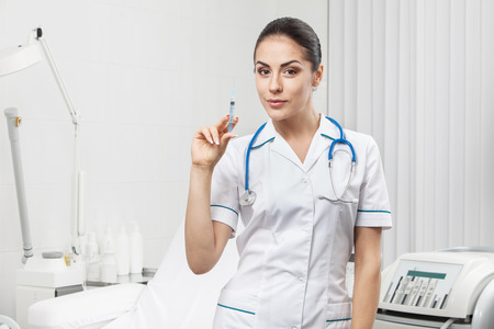 caucasian white: young nurse - beautiful brunette woman medical worker holding syringe Stock Photo