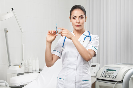 one female: young nurse - beautiful brunette woman medical worker holding syringe Stock Photo