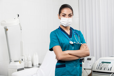 protective mask: young nurse - beautiful brunette woman medical worker wearing protective mask