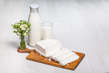 pasteurized: milk bottle and glass on wooden background, rural wildflowers bouquet, cottage cheese Stock Photo