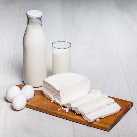kefir in bottles: milk bottle and glass on wooden background, cottage cheese, eggs Stock Photo