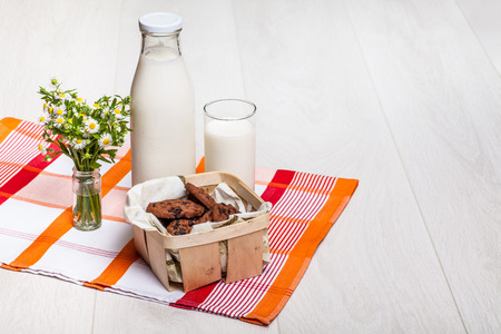 pasteurized: milk bottle and glass on wooden background, rural wildflowers bouquet