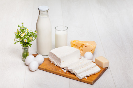 milk products: milk bottle and glass on wooden background, cottage cheese, eggs, Parmigiano Stock Photo