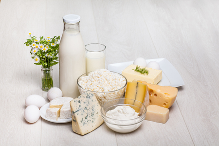 roquefort: dairy products - milk bottle and glass on wooden background, cottage cheese, eggs, camambert, Parmigiano, Roquefort