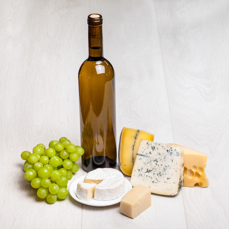roquefort: bottle of wine and different kinds of cheese on wooden background - cottage cheese, camambert, Parmigiano, Roquefort