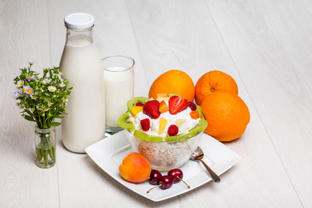 cottage cheese with strawberries, kiwi, raspberry and pineapple on wooden background close-up