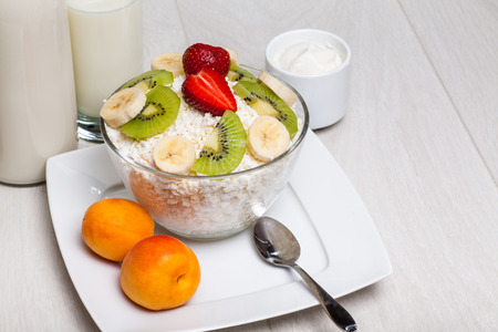 cottage cheese with strawberries, banana, kiwi on wooden background close-up