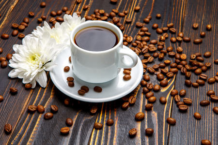 Still life with cup of coffee and flowers on dark wooden table Stock Photo