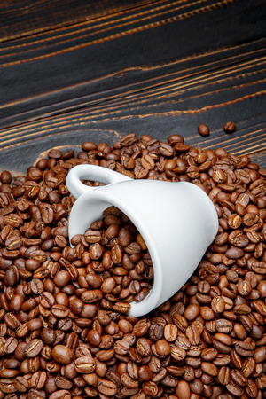 roasted coffee beans and cup on dark wooden background Stock Photo