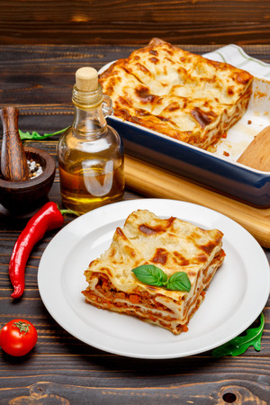 Portion of tasty lasagna on wooden backgound Stockfoto