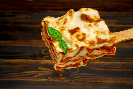 Portion of tasty lasagna on spatula