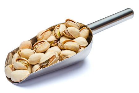 Scoop of Roasted pistachios nuts isolated on white background. Clipping path
