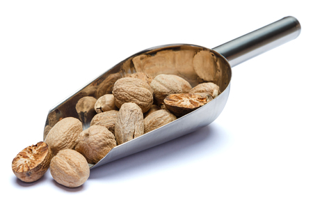 Scoop full of nutmegs isolated on white background. Clipping path