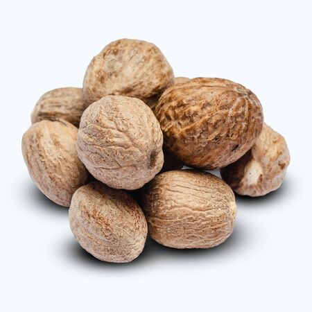 heap of nutmegs isolated on white background
