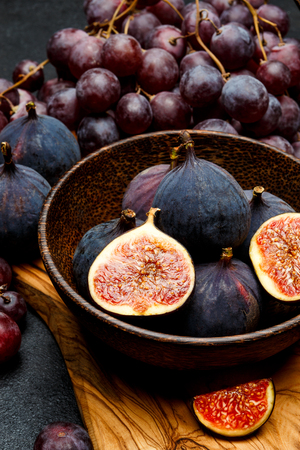 Ripe Grapes and Figs on dark concrete background