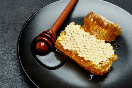 Honeycomb with honey on plate. dark concrete background
