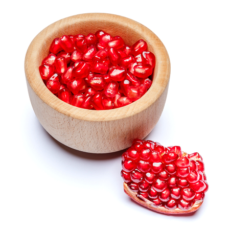 Pomegranate seeds in wooden bowl close-up Stock Photo