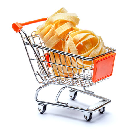 raw fettuccine ribbon pasta in shopping cart on white background