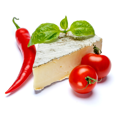 traditional french brie cheese, tomato and pepper on a white background Standard-Bild