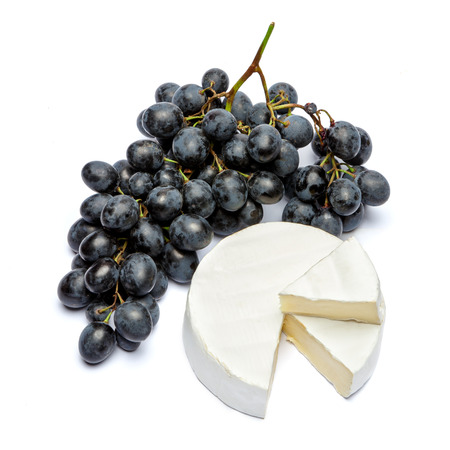 Round brie or camambert cheese and grapes on a white background Stock Photo
