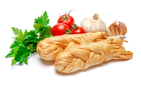 Smoked braided cheese and tomatoes on white background