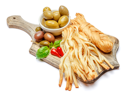 Smoked braided cheese and vegetables on white background Foto de archivo