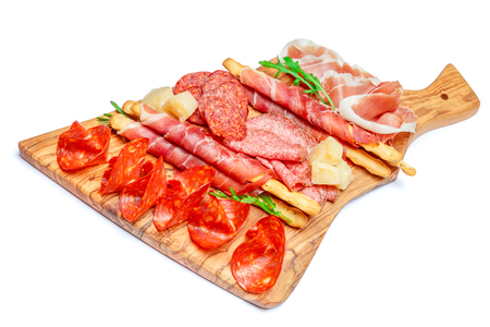 Cold smoked meat plate with pork chops, prosciutto, salami and bread sticks