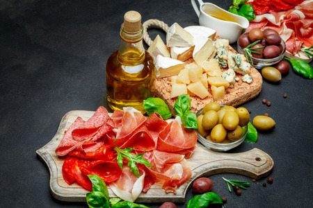 Traditional Italian products - prosciutto crudo or spanish jamon, cheese, olives