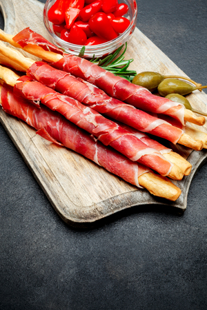 traditional italian snack prosciutto crudo bread sticks, peppers and capers
