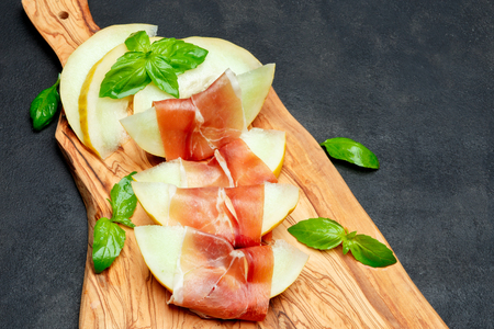 italian food with melon and prosciutto on wooden cutting board