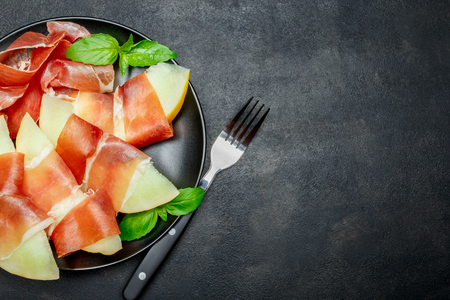 italian food with melon and prosciutto on the plate Standard-Bild