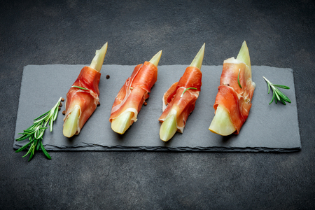 italian food with melon and prosciutto on stone board