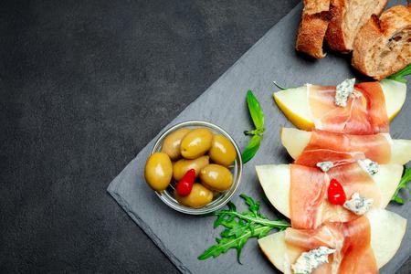 italian food with melon and prosciutto on stone board
