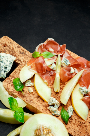 italian food with melon, prosciutto and cheese on cork cutting board