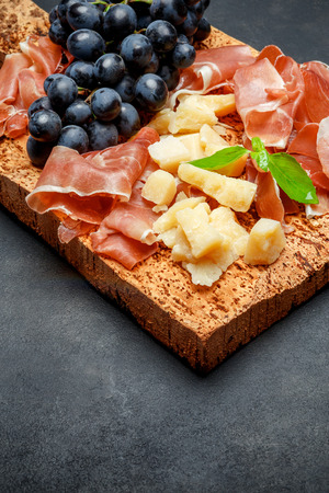 italian food with grapes, prosciutto and cheese on cork cutting board